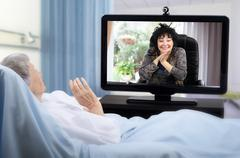 Senior patient has video chat on big monitor in hospital Stock Photos