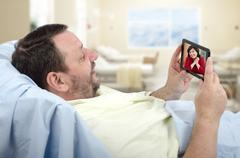 Bearded patient on hospital bed chatting by mobile phone Stock Photos