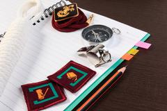 Orderliness white scout rope, compass, scouts badge and pencil on wooden tabl - stock photo