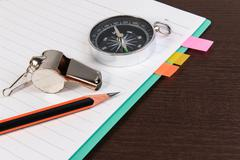 Metal whistle, pencil, compass with notebook on dark wooden background. Kuvituskuvat
