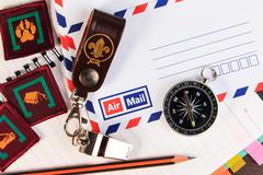 Metal whistle with leather keychain, compass, badge on envelopes background. - stock photo