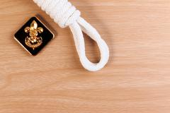Orderliness white scout rope with vintage boy scouts badge on wooden table. Stock Photos