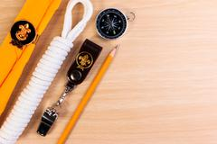 Metal whistle, scout scarf, rope, pencil and compass on wooden background. - stock photo