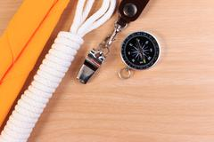 Orderliness white scout rope, scarf, whistle and compass on wooden table. Stock Photos