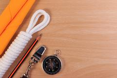 Orderliness white scout rope, scarf, whistle, pencil and compass on wooden ta Stock Photos
