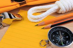 Orderliness white scout rope, scarf, whistle, compass, pencil and paper note - stock photo