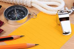 Orderliness white scout rope, whistle, compass, pencil and paper note on wood - stock photo