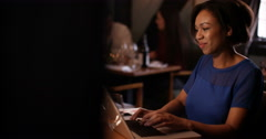 4K Thoughtful woman sitting alone in a bar & working on laptop at night - stock footage