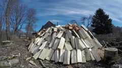Sun shining on big heap of cut firewood, time lapse 4K - stock footage