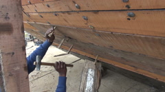 India, December 2012  - man working on big boat by river Ganges Stock Footage