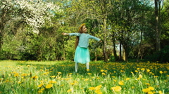 Cute girl 7-8 years old with wreath of dandelions on the head spinning Stock Footage