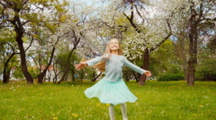 Cute girl child 7-8 years old with blond long hair spinning in the park Stock Footage