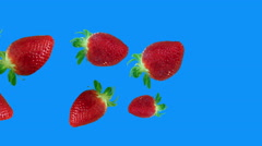 strawberries falling from left to right blue screen - stock footage