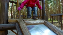 Child girl rolls down the hill. Child taps on the metal plate down. - stock footage