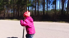 The girl child is gaining speed up scooter and falling onto the road. Stock Footage