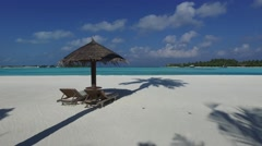 Palapa and sunbeds by sea on maldives beach Stock Footage