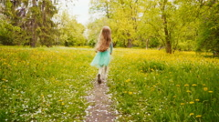 Happy girl spinning and running in the park in the spring Stock Footage