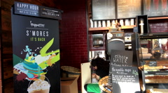 Worker stocking cups with happy hour sale sign at Starbucks coffee shop Stock Footage