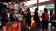 Customer buying coffee and paying by apple pay at Starbucks Stock Footage