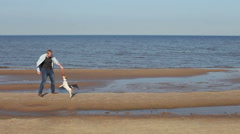 Man playing with the dog Jack Russell on the beach Stock Footage