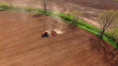 Springtime agricultural activity, tractor cultivating field Stock Footage