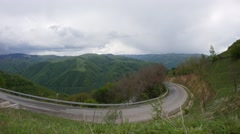 Clouds passing in speed over the high mountains with dense forests, on a road Stock Footage