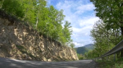 Asphalted road that descends on a mountain side through the green forest, lit Stock Footage