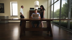 Man works on laptop, co-workers join Stock Footage