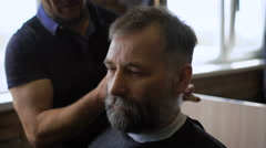 Stylish Barber works with the haircut. Client aged with gray hair and beard - stock footage
