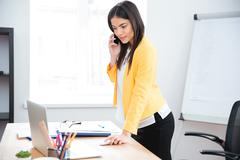 Businesswoman talking on the phone in office - stock photo