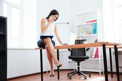Businesswoman working with phone and laptop computer in office - stock photo