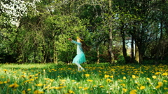 Whirling girl 7-8 years with wreath of dandelions on the head spinning Stock Footage