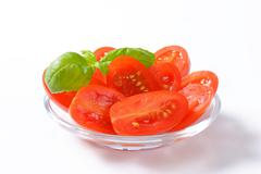 Halved fresh oval-shaped red tomatoes - stock photo