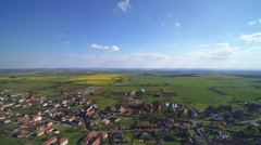 Aerial view of village and farm fields in spring - stock footage