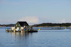 Fish farm with floating house, Aversund Fjord, near Bergen, Hordaland, Norway, - stock photo