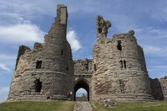Walkers arrive at historic Dunstanburgh Castle, Northumberland, England, United - stock photo