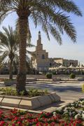 Palm trees and flower beds along Al-Corniche, waterfront promenade, with Qatar - stock photo