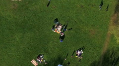 Camera flying over summer park with resting families Stock Footage