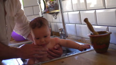 Father washing his baby in sink in kitchen Stock Footage