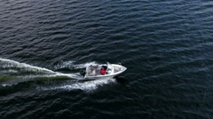 Small powerboat riding on water surface, slow motion aerial view from drone Stock Footage