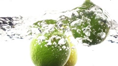 Limes and lemons dropping into water in slow motion. - stock footage