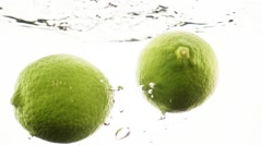 Two limes falling into water in slow motion. - stock footage