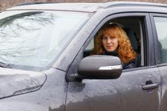 Young red-haired woman looks through the car window - stock photo