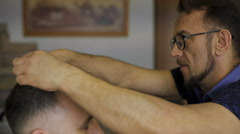 hairdresser  cuts   hair  with scissors on crown client in  professional - stock footage