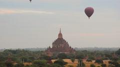 Hot air balloon over ancient templeat Bagan at dawn. Stock Footage