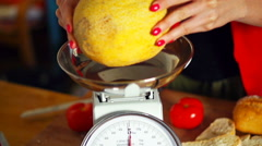Woman checking weight of melon on scales in kitchen Stock Footage