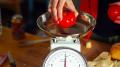Woman checking weight of tomatoes on scales in kitchen Stock Footage