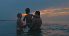 Young family enjoying sea bathing in the evening Stock Footage