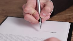 Male hand signing a document. Stock Footage