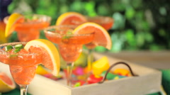 Spicy grapefruit margarita on ice in margarita glasses on the table in the garde Stock Footage